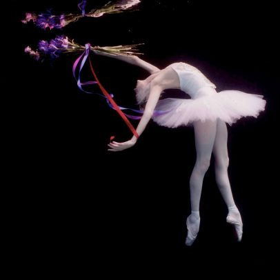 ballerina dancing underwater with a bouquet and a tutu