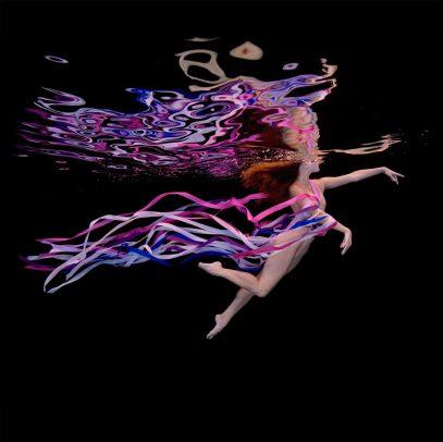 girl swimming underground with purple stripes