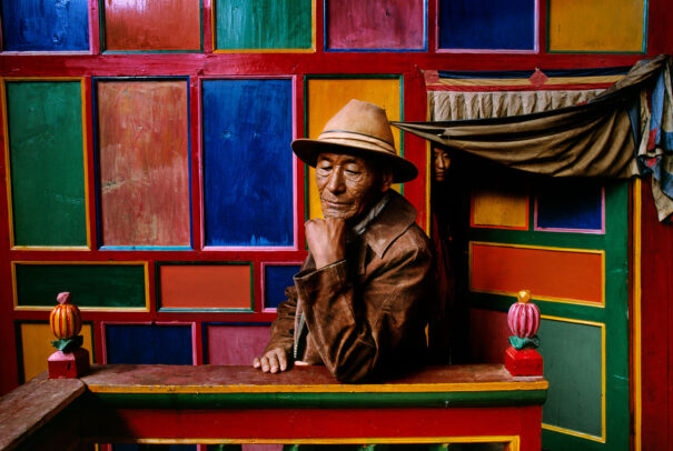 A tibetan man in front of a colorful wall