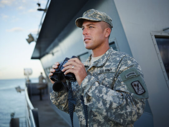 american soldier on a ship holding a binoculars
