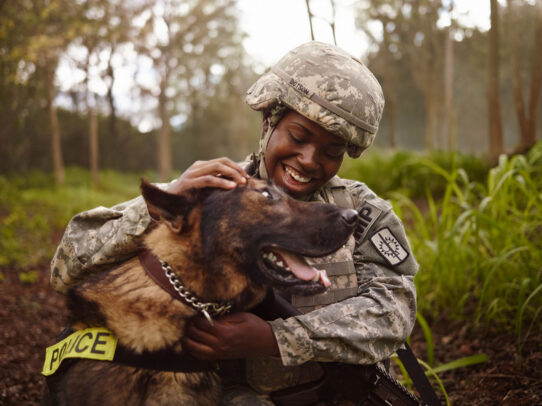 female american soldier petting a dog