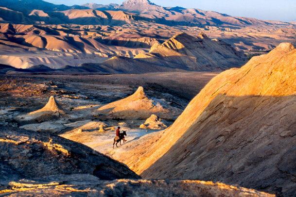 Man rides a donkey through the afghan desert
