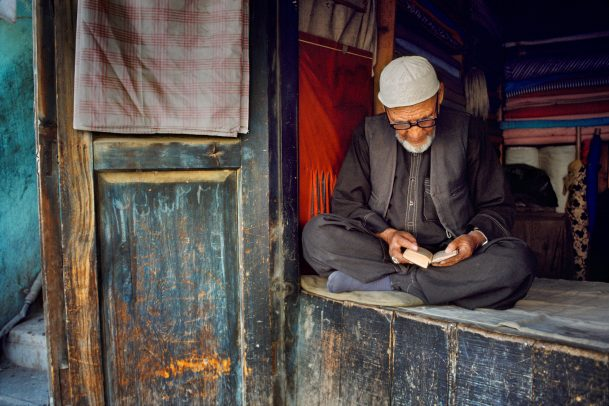 fabric vendor man sits and reads a book