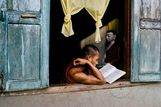 Monk reads scripture at window