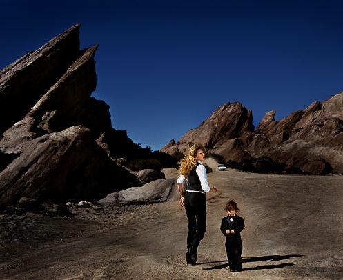 woman walking in mountain setting with a child