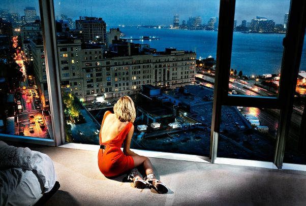 woman sitting in a penthouse looking through window towards the docks of the city