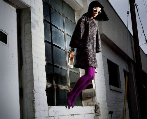 woman with coat and purple thights jumping out of the window