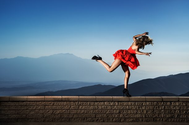 Woman in red dress and high heels dancing on a wall