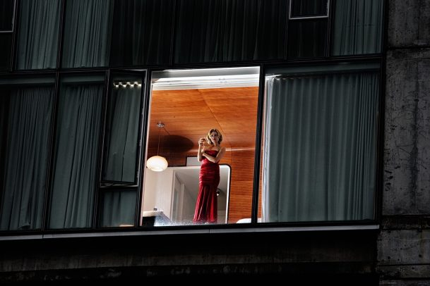 woman in long red dress holding a glass of wine and looking down of a window