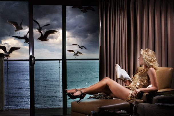 woman with heels and golden dress reading near a window and looking at see and some seagulls flying