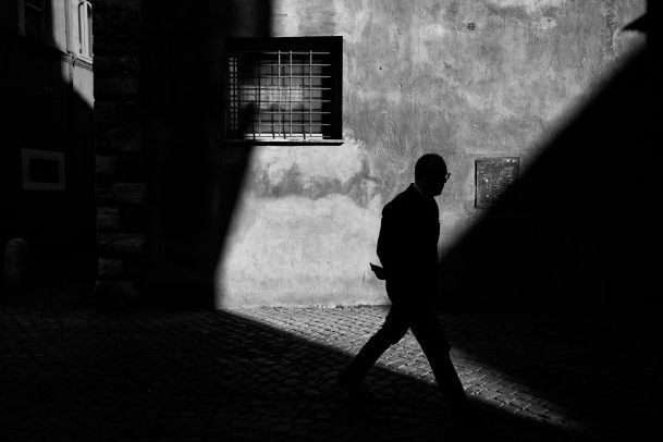 man walking in shadow of the street