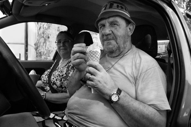 man eating an ice cream in his car with a lady