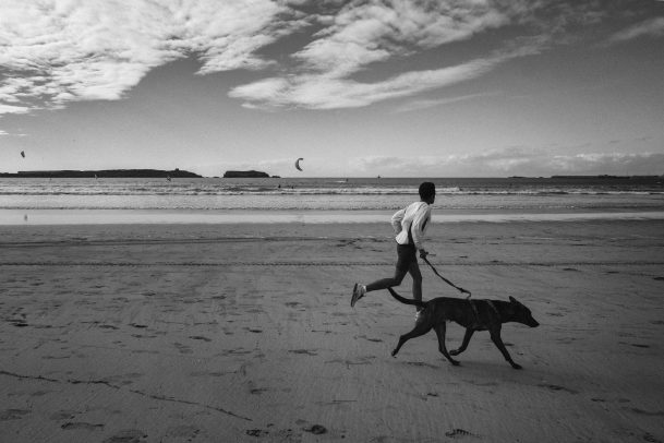 Person running on the beach with dog