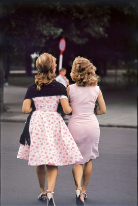 two women wearing pink dresses walking