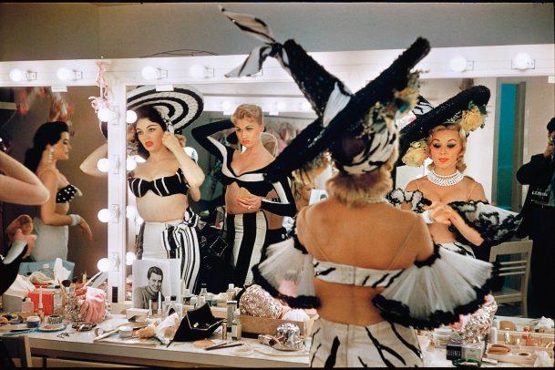 Showgirls with big hat getting ready