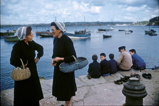 women with traditional breton cap chatting on the dock