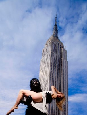 Person with monkey costume holding a girl with white dress and Empire State Building on the background