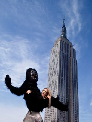 blond girl holding a person with a costume of monkey with Empire State Building in background