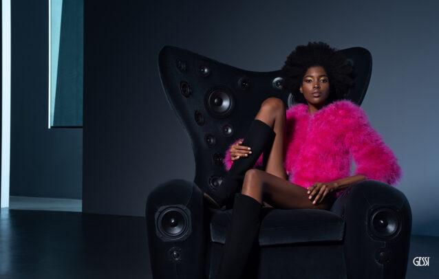 black woman wearing pink fur on a black armchair with speakers for Gessi by Susi Belianska