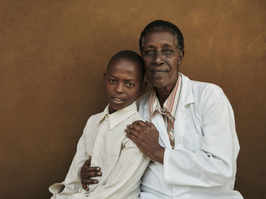 a doctor and his young patient posing for Novartis annual report by Joey L.