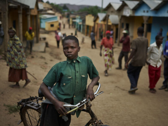 boy with his bicycle in an ethiopian street during Novartis annual report by Joey L.