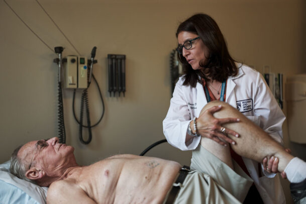 A doctor examining her patient who lies on a bed during Novartis annual report by Joey L.
