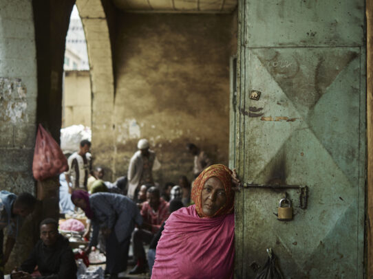 a woman leaning on a door in a market during Novartis annual report by Joey L.