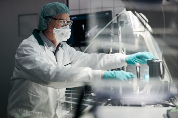 a doctor with mask, cap and gloves in laboratory during Novartis annual report by Joey L.