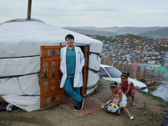 a doctor leaning on the entrance of a yurta during Novartis annual report by Joey L.