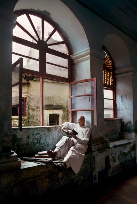 A man sits and reads by a window
