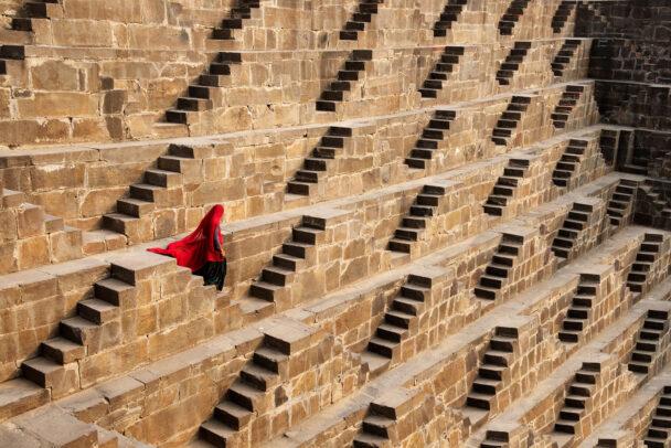 A woman walks down many steps.