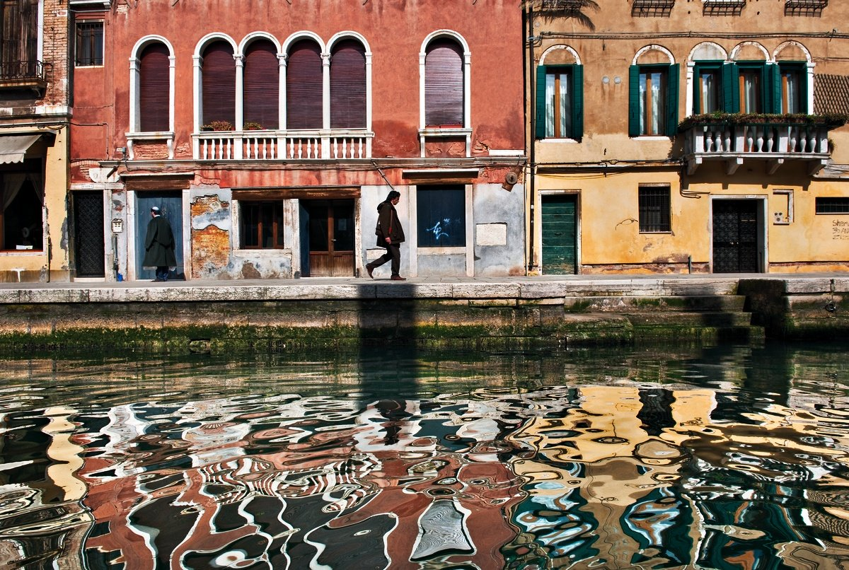 colorful venetian buildings' reflections in a canal