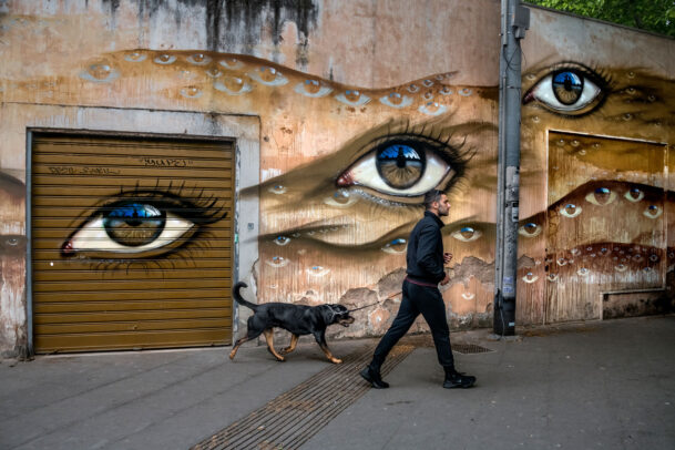 Man with dog passing mural in rome