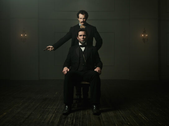 Jesse Johnson as John Wilkes Booth standing with a gun in hand and Billy Campbell as Abraham Lincoln sitting on a chair