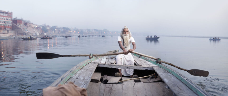 old man on a boat of a river in India