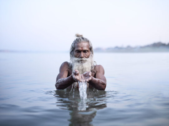 old man with white beard picking up water from the river in India