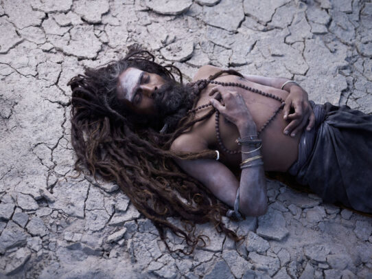 man with long dreadlocks lying on the ground