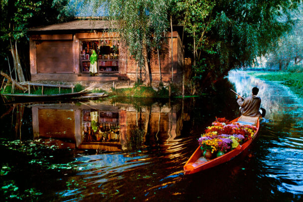 A flower vendor rowing next to a shop on a lake