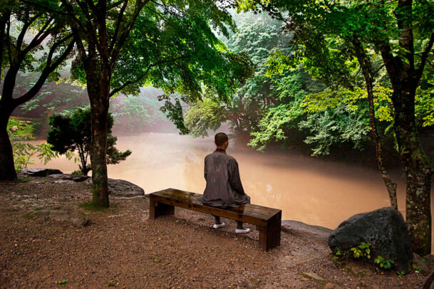 Buddhist monk sitting on a bench in Songnisan National Park