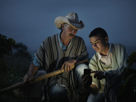 a boy showing to his father something on his phone at dusk for Lavazza Calendar 2016 by Joey L