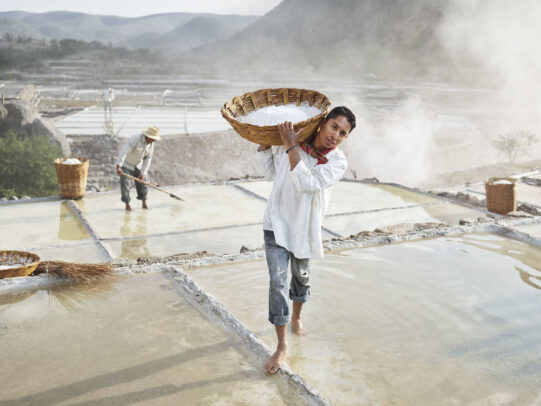 man holding a basket full of salt in a saltwork