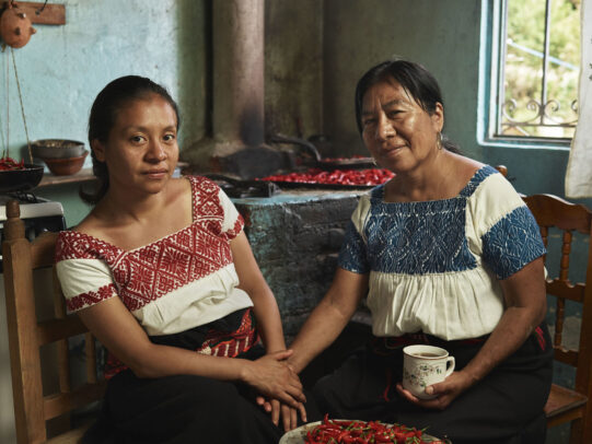 mother and daughter in traditional dresses holding hands and a cup of coffee