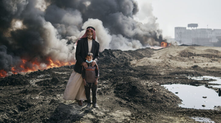 a fire with black smoke behind an old man and a child in Iraq
