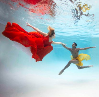 a couple dancing underwater with colorful dress