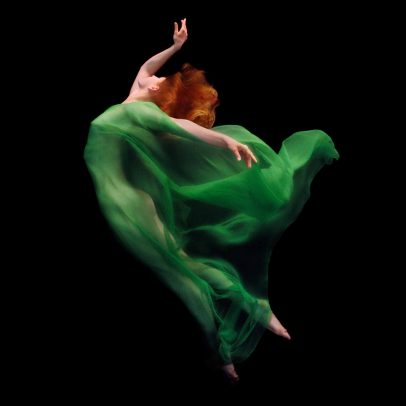 redhead girl dancing underwater with a green dress