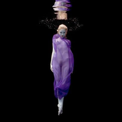 blonde girl underwater with purple dress