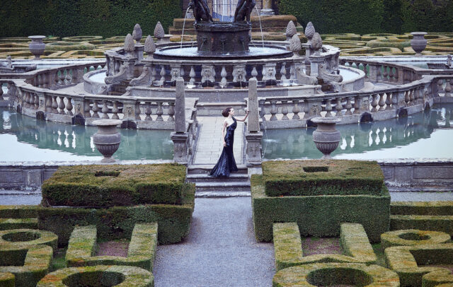 Woman with long black dress near the fountain of the garden of Villa Lante