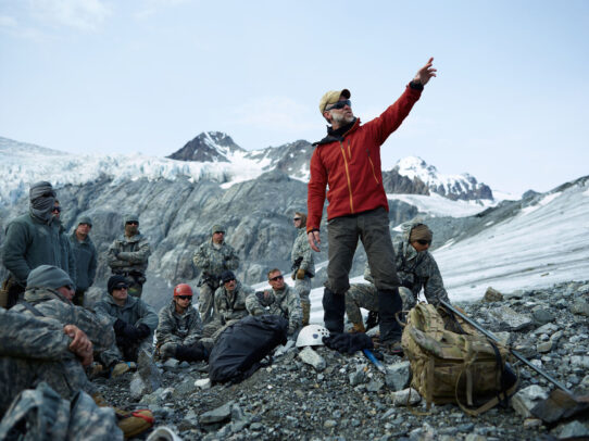american soldier with red jacket pointing out on the mountain