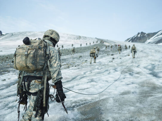 american soldiers walking and training on a glacier