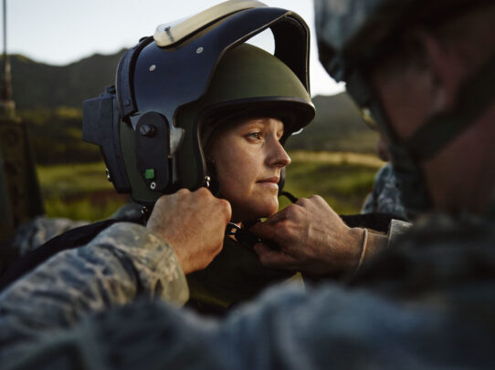 female american soldier being helped in wearing helmet
